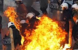 A petrol bomb explodes at riot police in Athens during riots