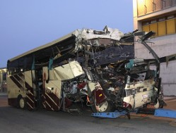 The wreckage of a bus that crashed into a motorway tunnel is pulled into the town of Sierre (Reuters