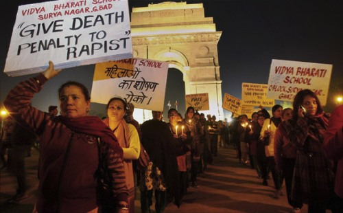 Delhi_People hold placards as they participate in a candlelight vigil at India Gate