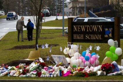 A student is consoled after he placed flowers on a memorial at the entrance to Newtown High School in Newtown, Conn., on Dec. 18, 2012. (REUTERS)