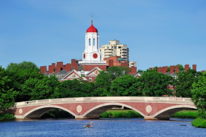 John W. Weeks Bridge and clock tower over Charles River in Harvard University campus in Boston with trees, boat and blue sky
