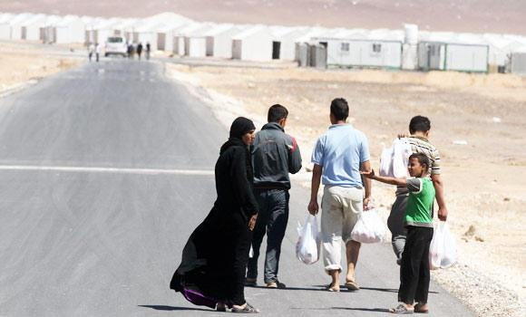 A Syrian refugee family walks towards the new Syrian camp of Azraq, which stretches for 9 miles, and lies 55 miles from the Syrian border in Jordan, on Wednesday. (AP)