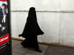 """A Muslim woman wearing a burqa walks through Birmingham, United Kingdom, in 2010. At least six schools in the city have been implicated in a """"Trojan Horse"""" plot by extremists to """"Islamize"""" secular state education."""