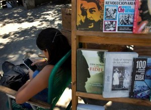 A book street vendor passes the time on her smart phone as she waits for customers in Havana, Cuba, Tuesday, April 1, 2014. (AP Photo/Ramon Espinos