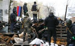 Pro-Russian men stand guard at a barricade near the police headquarters in Slaviansk