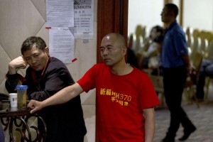 A relative of Chinese passengers onboard Malaysia Airlines Flight 370 stands at the entrance to a meeting room wearing a T-shirt which reads 'Pray for MH370 safe return' in Beijing, China, Wednesday (AP photo)