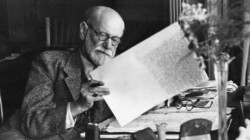 Sigmund Freud, 1856-1939, Austrian psychiatrist, in the office of his Vienna home looking at a manuscript