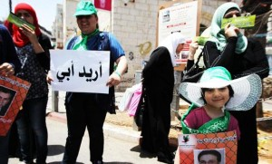 """A Palestinian supporters of Hamas hold a poster reading in Arabic: """"I want my father"""" while others hold pictures of Palestinians held in Israeli jails during a demonstration in the West bank city of Ramallah in support of prisoners on hunger strike on Saturday. (AFP)"""
