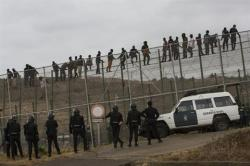 Spanish police officers stand guard as sub-Saharan migrants sit on top of a metallic fence that divides Morocco and the Spanish enclave of Melilla, Saturday, May 17, 2014. S(AP Photo/Santi Palacios)