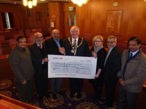 Members of the Ahmadiyya Muslim community with West Oxfordshire District Council chairman Councillor Normal MacRae and representatives from Helen and Douglas House Hospice.