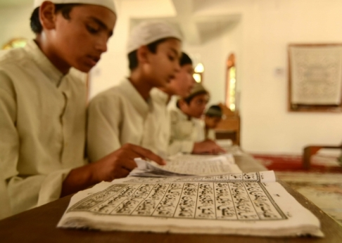Children reciting the Quran at a religious institute. Photo does not depict the madrassa set up in Malta