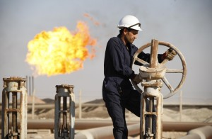 A worker adjusts the valve of an oil pipe at West Qurna oilfield in Iraq's southern province of Basra i
