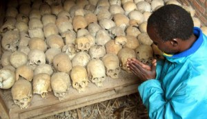 A Rwandan survivor of the 1994 genocide prays over the bones of victims at a mass grave in Nyamata, Rwanda, April 6, 2004. Photo by AP