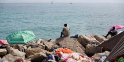 Migrants sit on the rocky beach at the Franco-Italian border in Ventimiglia, Italy, during the holy month of Ramadan, on Friday (AP photo)