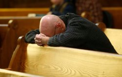 Father Bill Carmody kneels in a pew during a vigil to mark Friday's shooting at a Planned Parenthood clinic in a church Saturday, Nov. 28, 2015, in Colorado Springs, Colo. (AP Photo/David Zalubowski)