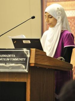 Mlahat Mahmood, 11, of Troy reads an excerpt from the Quran at the Stop The CrISIS: What is the Pathway to Peace symposium. Robin Buckson, The Detroit News