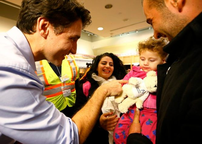 Syrian refugees are greeted by Canada's Prime Minister Justin Trudeau on their arrival from Beirut at the Toronto Pearson International Airport