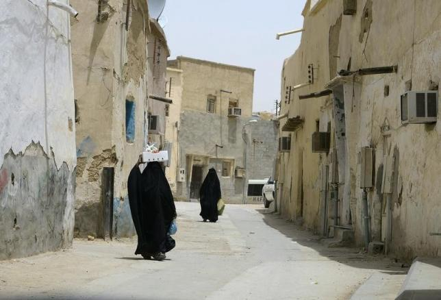 Veiled women carry vegetables as they walk along a street at the neighbourhood of Shmeisy