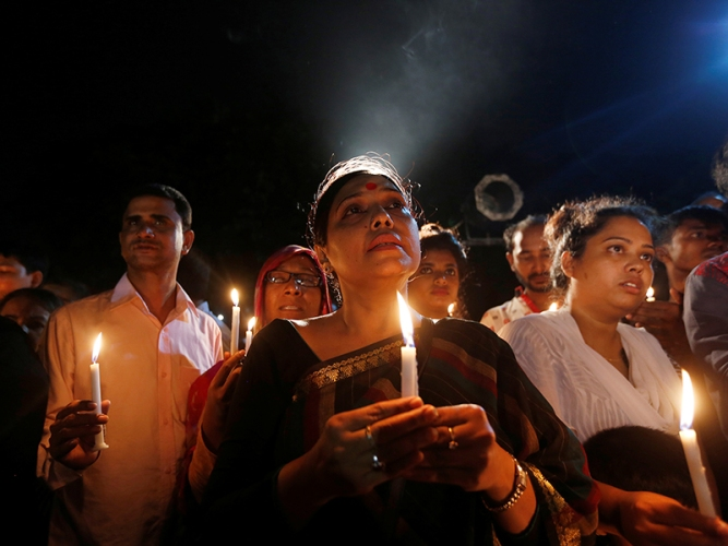 People attend a candle light vigil for the victims of the attack on the Holey Artisan Bakery and the O'Kitchen Restaurant, in Dhaka