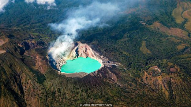 Aerial photo of active volcano Ijen in East Java - largest highly acidic crater lake in world with turquoise sulphuric water.