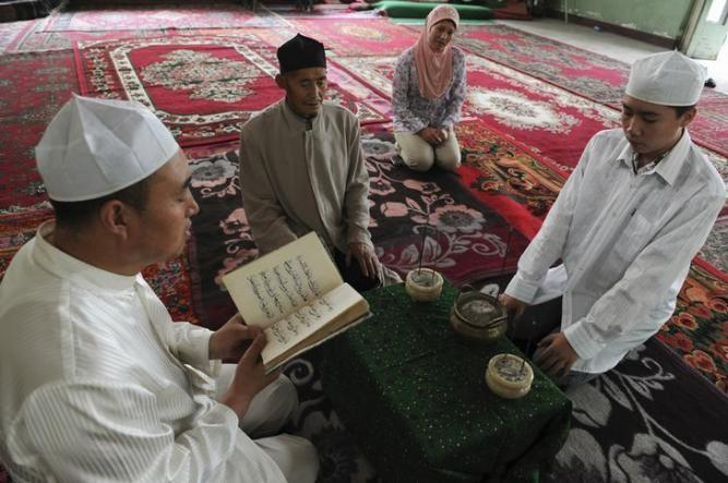 A Muslim man from the Chinese Hui minority reads the Koran as others listen in the sitting room in Aksu