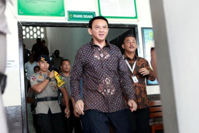 Jakarta's governor Basuki Tjahaja Purnama walks outside the court room shortly after his trial at the North Jakarta District Court in Jakarta, Indonesia