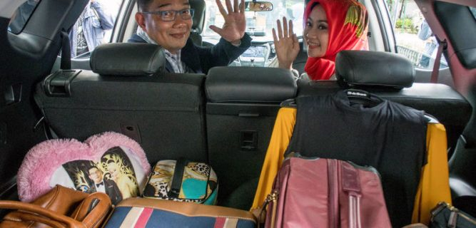Bandung Major Kamil and his wife Atalia wave to reporters as they sit in his car in Bandung