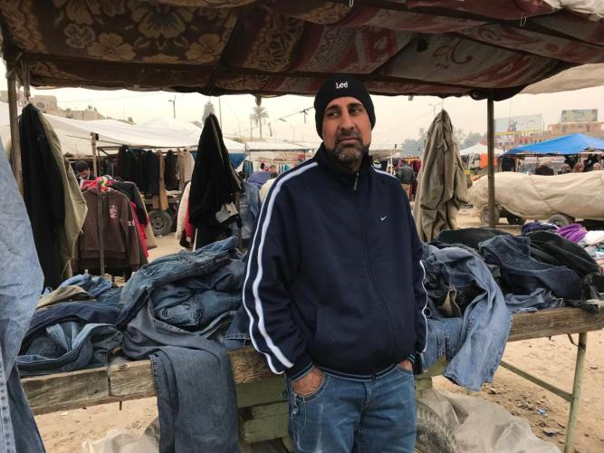Moayad stands in front of the market stall where he sells second-hand jeans in al-Nabi market in the east of Mosul