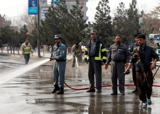 Afghan fire fighters clean the site of a suicide bomb attack near a Shi'ite mosque in Kabul