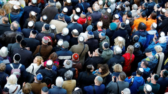 People wear kippas as they attend a demonstration in front of a Jewish synagogue in Berlin