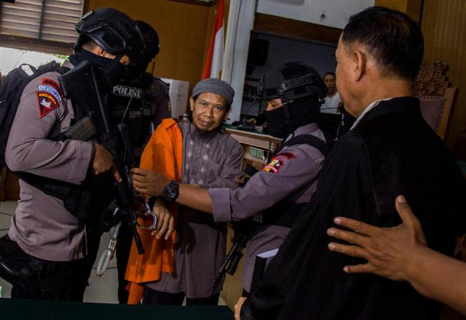 Policemen guard Islamic cleric Aman Abdurrahman inside a courtroom in Jakarta, Indonesia