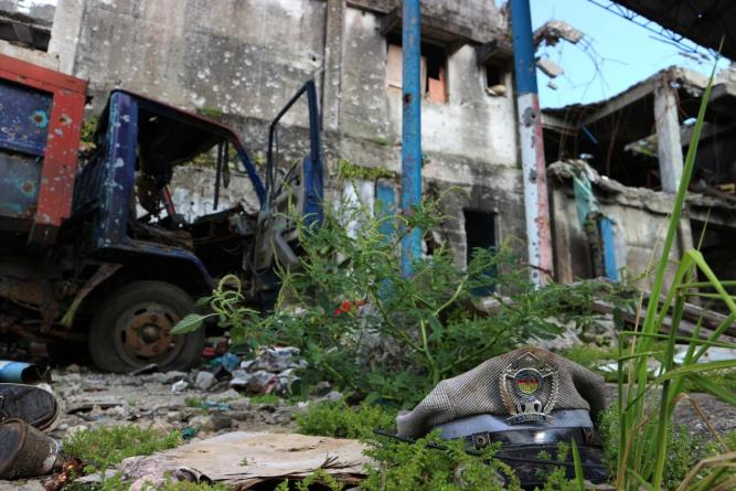 A jail police officer's cap lies among the debris and ruins of a destroyed prison in Marawi