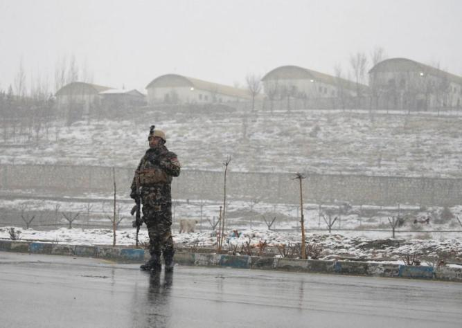 An Afghan security force member stands guard in front of the Marshal Fahim military academy in Kabul, Afghanistan