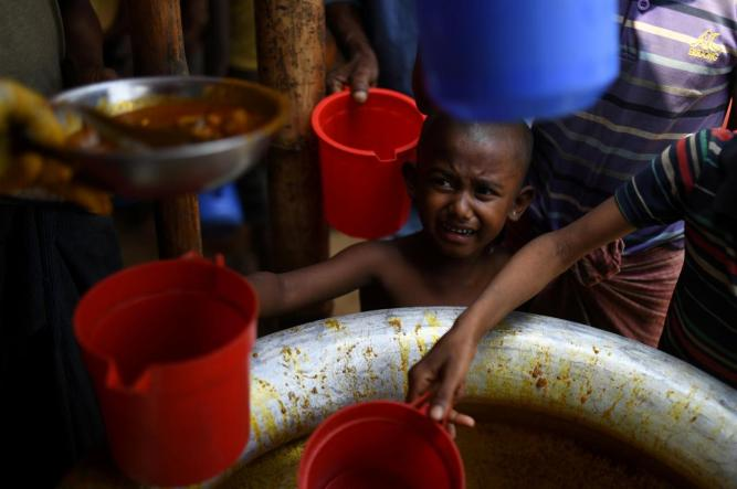 FILE PHOTO: Rohingya refugee child waits for rations
