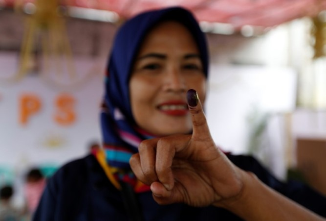 An Indonesian woman shows her ink-stained finger after casting her vote during regional elections in Tangerang