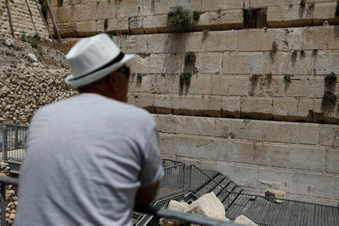 A man looks at a stone that fell off the Western Wall in Jerusalem's Old City