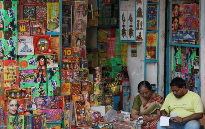 A woman and her son sit at their firecracker shop in the old quarters of Delhi