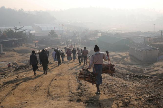 FILE PHOTO: Rohingya refugees walk at Jamtoli camp in the morning in Cox's Bazar