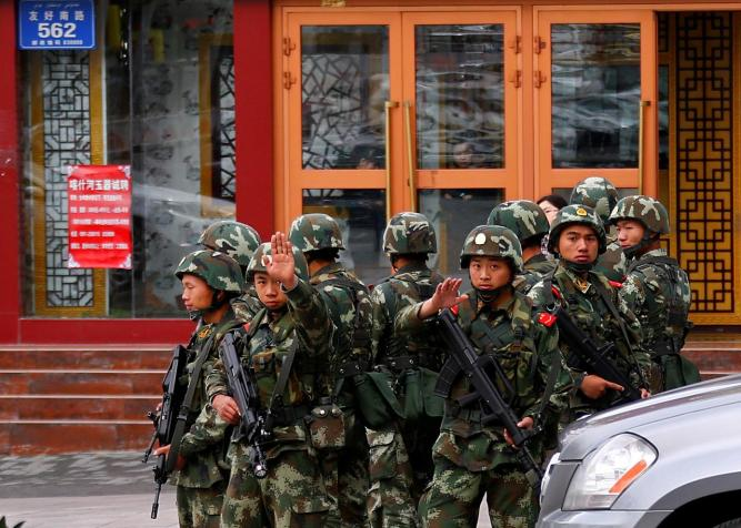 FILE PHOTO: Paramilitary policemen gesture to stop a photographer from taking pictures as they stand guard after explosives attack hit downtown Urumqi on Thursday, in Xinjiang Uighur Autonomous Region