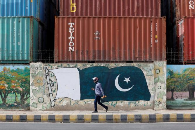 A man walks past a wall of a shipping container's yard painted with a national flag ahead of Pakistan's Independence Day, in Karachi