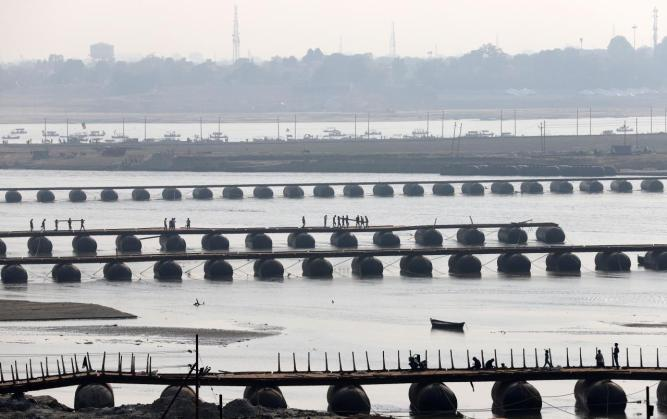"Labourers work on an under-construction pontoon bridge spanning the river Ganga ahead of the ""Kumbh Mela"", or the Pitcher Festival, in Allahabad"