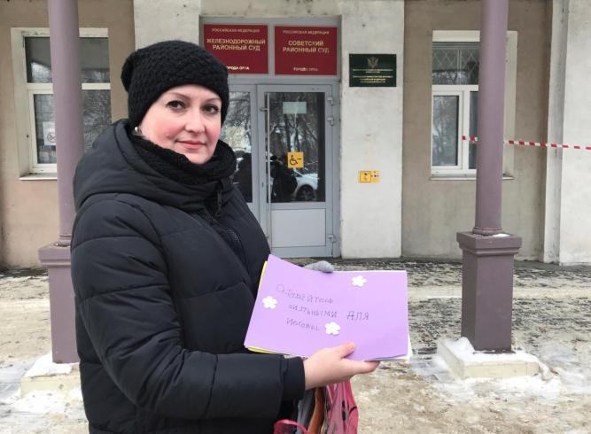Irina Christensen holds letters of support for her husband outside a court building in Oryol