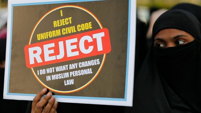 A Muslim woman displays a placard during a protest against a bill passed by India's lower house of Parliament that aims at prosecuting Muslim men who divorce their wives through the