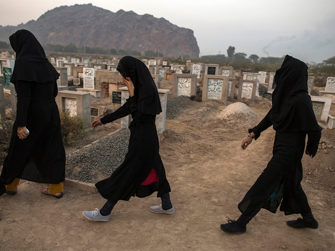 Ahamdi women walk past graves at the Ahmadi graveyard in Rabwa
